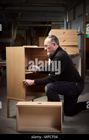 Cabinetmaker working on his handmade furnitures - Stock Photo