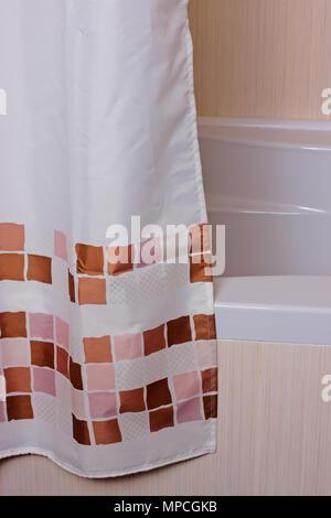 curtain in the bathroom near the tiled bath - Stock Photo