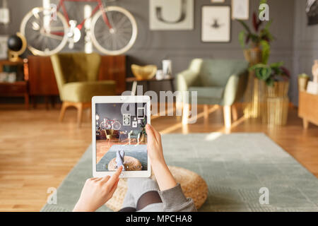A woman relaxing holding a tablet and using a touch screen while comfortably lying down on a green carpet in a vintage flat interior with blurred back - Stock Photo