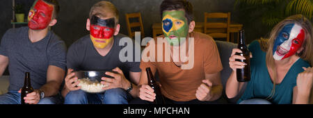 International football fans with painted faces watching tv - Stock Photo