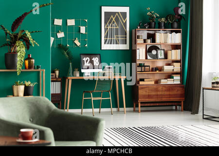Gold chair at desk with desktop computer in green, cozy apartment interior with poster - Stock Photo