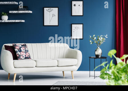Leather sofa, floral paintings on the blue wall and flower in a vase in a living room interior - Stock Photo