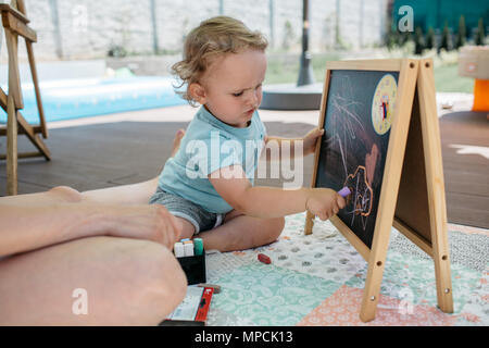 A toddler enjoying himself drawing on a chalkboard. A little boy scribbling with a chalk on a chalkboard. - Stock Photo