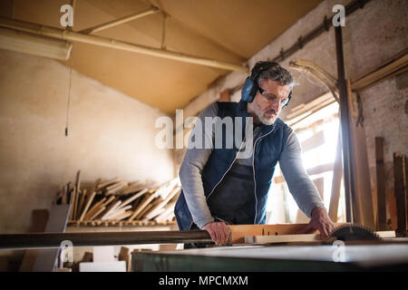 A man worker in the carpentry workshop, working with wood. - Stock Photo