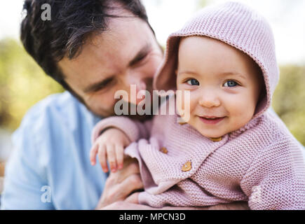 A father with his toddler daughter outside in spring nature. - Stock Photo