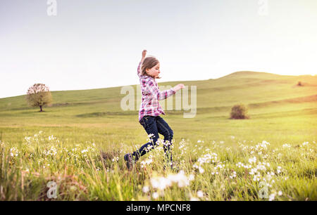 A small girl having fun outside in nature. - Stock Photo