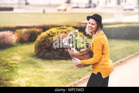 Young woman with flowers in a basket in sunny spring town. - Stock Photo