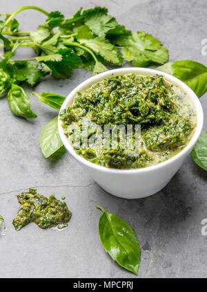 Green chimichurri parsley basil sauce. Slate background - Stock Photo