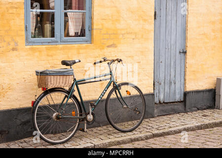 Bicycle at the door of an Aeroskobing home: A utility rocky bicycle stands ready at the door of a yellow brick home in the old town of AEroskobing - Stock Photo