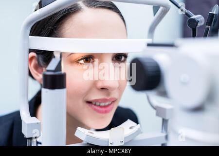 Woman having eyes measured with test device - Stock Photo