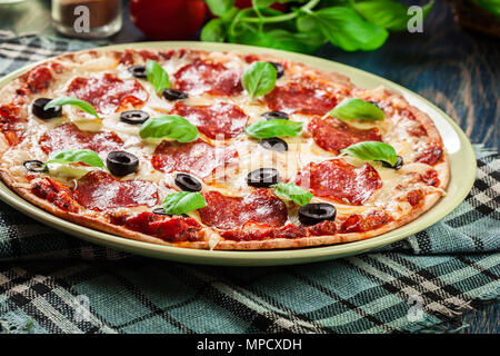 Pizza pepperoni with olives served on a plate - Stock Photo