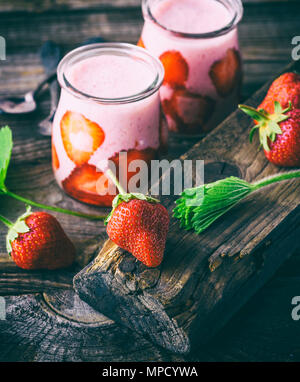 a ripe red strawberry and two glass jars of smoothies on a gray wooden table - Stock Photo