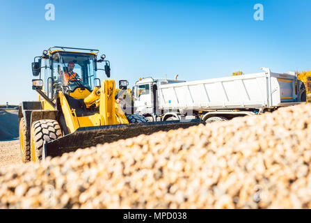 Construction workers doing earthworks with wheel loader - Stock Photo