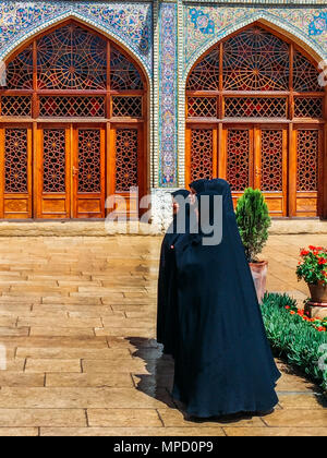 Isfahan, Iran - April 22, 2018: Traditionally dressed Iranian women outside the Historic Imam Mosque at Naghsh-e Jahan Square, Isfahan,Iran - Stock Photo