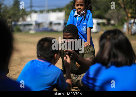 U.S. Marine Corps Cpl. Babdi Mohamed, a motor transport operator with Combat Logistics Battalion 4, plays with students at the Juksamed School, in Rayong Province, Thailand, during exercise Cobra Gold, Feb. 8, 2017. Cobra Gold 2017, in its 36th iteration, includes a specific focus on humanitarian civic action, community engagement, and medical activities conducted during the exercise to support the needs and humanitarian interests of civilian populations around the region. (U.S. Marine Corps photo by Cpl. Wesley Timm) - Stock Photo