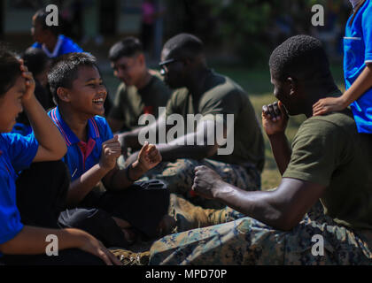 A student and U.S. Marine Corps Cpl. Babdi Mohamed, a motor transport operator with Combat Logistics Battalion 4, play at the Juksamed School, in Rayong Province, Thailand, during exercise Cobra Gold, Feb. 8, 2017. Cobra Gold 2017, in its 36th iteration, includes a specific focus on humanitarian civic action, community engagement, and medical activities conducted during the exercise to support the needs and humanitarian interests of civilian populations around the region. (U.S. Marine Corps photo by Cpl. Wesley Timm) - Stock Photo