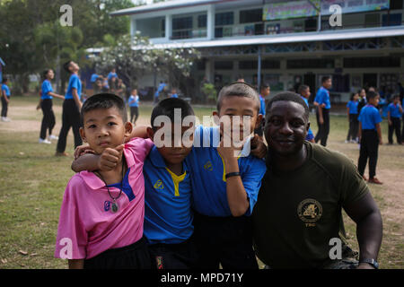 U.S. Marine Corps Cpl. Babdi Mohamed, a motor transport operator with Combat Logistics Battalion 4, takes a photograph with students at the Juksamed School, in Rayong Province, Thailand, during exercise Cobra Gold, Feb. 8, 2017. Cobra Gold 2017, in its 36th iteration, includes a specific focus on humanitarian civic action, community engagement, and medical activities conducted during the exercise to support the needs and humanitarian interests of civilian populations around the region. (U.S. Marine Corps photo by Cpl. Wesley Timm) - Stock Photo