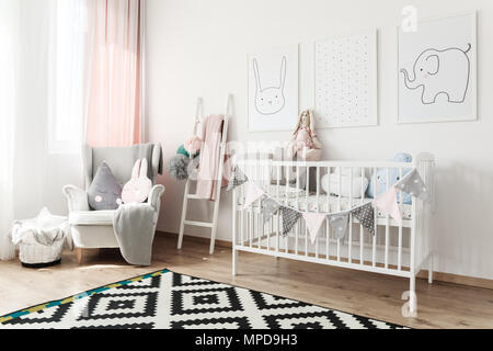 Black and white carpet in scandi child's room with white bed, grey armchair and ladder with pompons - Stock Photo