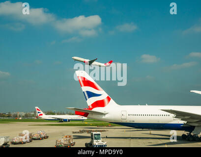 British Airways Boeing 777 on airport apron, Virgin Atlantic aeroplane taking off in blue sky, Terminal 5, Heathrow airport, London, England, UK - Stock Photo