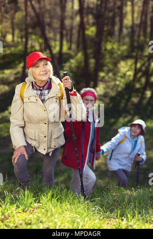 Happy hikers walking in the woods - Stock Photo