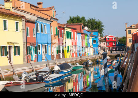 Brightly coloured fishermen's cottages reflected in a canal, Burano, Venice, Italy in early morning light. The island is a popular tourist attraction - Stock Photo