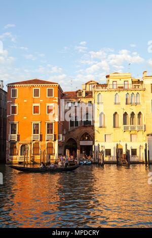 Tourists enjoy a romantic gondola ride at sunset, Grand Canal, Cannaregio, Venice,  Veneto, Italy passing Camiello del Remer with local Venetians enjo - Stock Photo