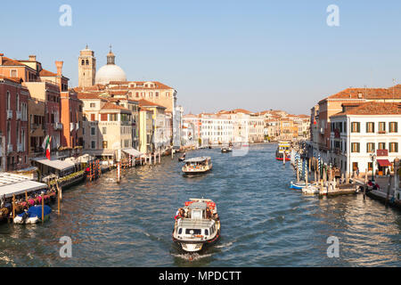View of Grand Canal (Canal grande) at sunset from Scalzi Bridge, Venice, Veneto, Italy with vaporettos, (water bus, waterbus) full of tourists - Stock Photo