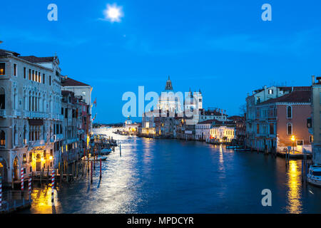 Full moon at blue hour over the Grand Canal, Venice, Veneto, Italy with Basilica di Santa Maria della Salute and a reflection on the water - Stock Photo