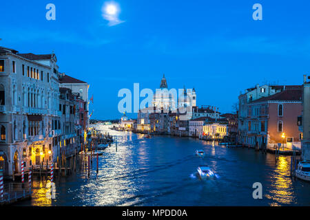 Full moon at blue hour over the Grand Canal, Venice, Veneto, Italy with Basilica di Santa Maria della Salute. Reflection on the water and a water taxi - Stock Photo