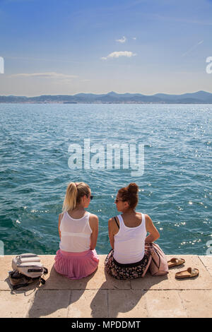 Two young women enjoying  sitting talking in the sunshine on the seafront promenade in the Adriatic coast port of Zadar Croatia - Stock Photo