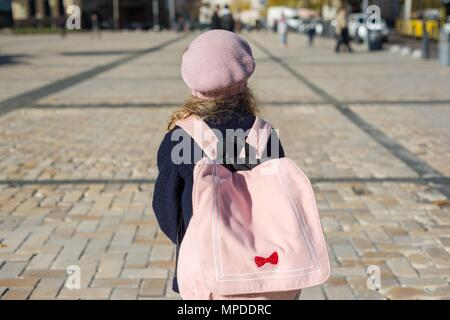 Stylish little girl with a backpack, in a coat and french beret run to school. Back view - Stock Photo
