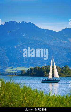 Lake Chiemsee with sailboat and mountain Kampenwand in the background, Bavaria, Germany, Europe - Stock Photo