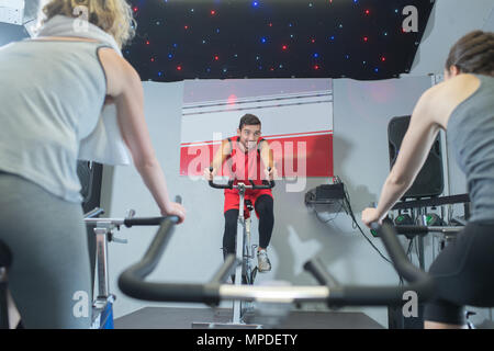 fit people in a spin class at the gym - Stock Photo