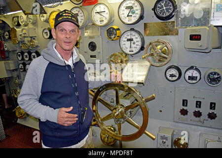 US Navy Vietnam Veteran hand on the throttle in the engine room, control room, of the USS Midway aircraft carrier Museum, San Diego, California - Stock Photo