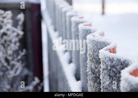 Wavy fence covered with frost in perspective - Stock Photo