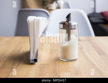 Glass dispenser with sugar and metal napkin stand on table in cafe - Stock Photo