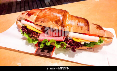 Croissant Sandwich with ham, cheddar cheese, cherry tomato and greens. fast food concept. - Stock Photo
