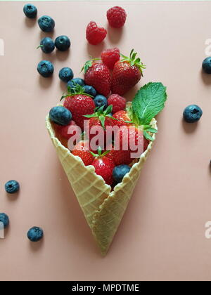 Fresh fruit and berries in waffle cones on paper. Flat lay, top view - Stock Photo