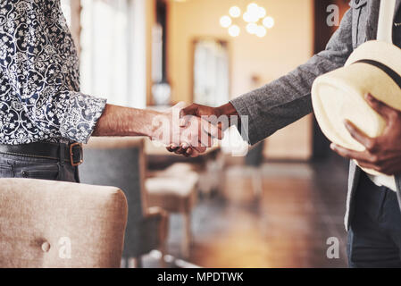 Black and white entrepreneurs shaking hands, satisfied multi-ethnic casual businessmen binding business deal with handshake, thanking for help support in successful teamwork - Stock Photo