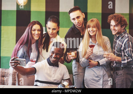 Friends having fun at restaurant.Two boys and four girls drinking making selfie, making peace sign and laughing. On foreground woman holding smart phone. All wear casual clothes - Stock Photo