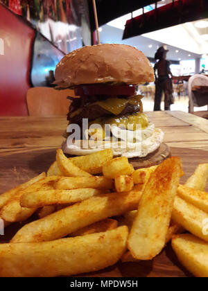 Tall Hamburger with Potatoes served at Restaurant. FastFood. - Stock Photo
