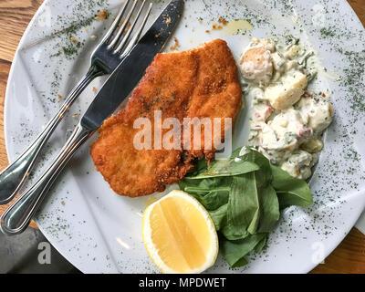 Chicken Schnitzel with potato salad and lemon served at restaurant. Organic Food. - Stock Photo