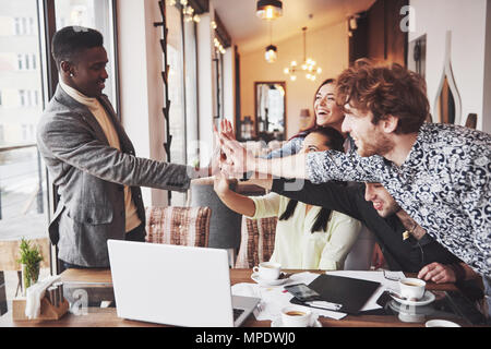 Happy young entrepreneurs in casual clothes at cafe table or in business office giving high fives to each other as if celebrating success or starting new project - Stock Photo