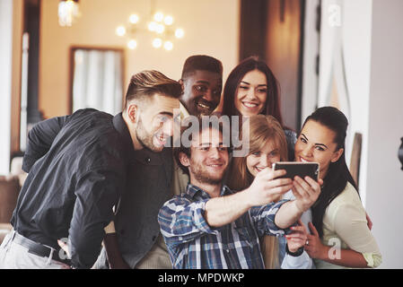 Multiracial people having fun at cafe taking a selfie with mobile phone. Group of young friends sitting at restaurant taking self portrait with smart phone - Stock Photo