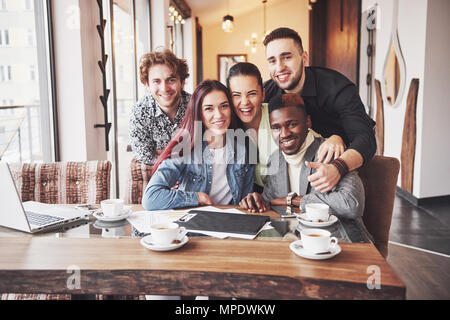 Multiracial people having fun at cafe taking a selfie with mobile phone. Group of young friends sitting at restaurant - Stock Photo