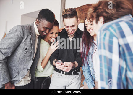 Portrait of cheerful young friends looking at smart phone while sitting in cafe. Mixed race people in restaurant using mobile phone - Stock Photo