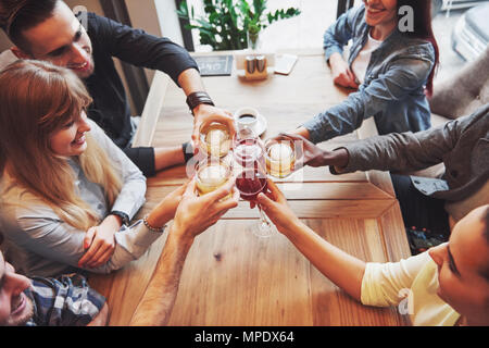 View from the top. Hands of people with glasses of whiskey or wine, celebrating and toasting in honor of the wedding or other celebration - Stock Photo
