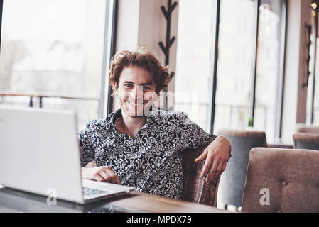 Young handsome man sitting in office with cup of coffee and working on project connected with modern cyber technologies. Businessman with notebook trying to keep deadline in digital marketing sphere - Stock Photo
