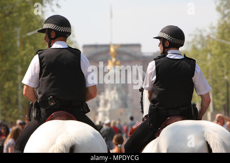 Mounted Police patrol the Mall with Buckingham Palace backdrop celebrating the Royal wedding of Prince William and Catherine Middleton on the 29th April 2011 at Westminster Abbey London UK - Stock Photo