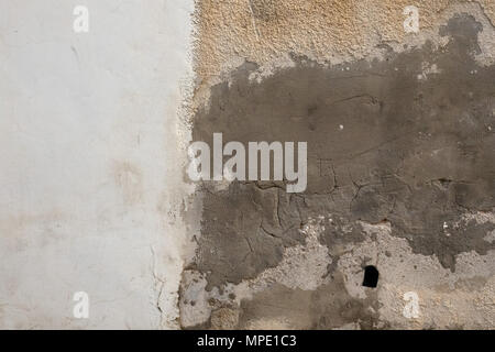 Abstract background texture old wall yellow plaster, smeared with gray clay, left a strip of white paint and an empty space for text.